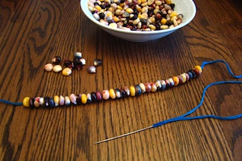 stringing autumn corn into a necklace