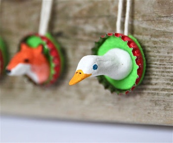 bottle cap ornament with a spring animal made from clay inside