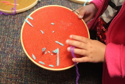 burlap stretched in an embroidery hoop beginning stitchery for kids