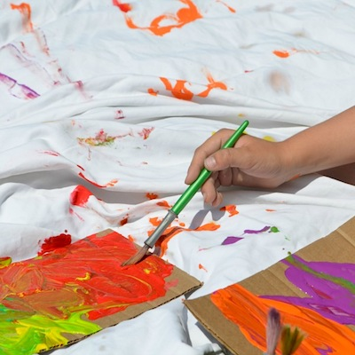 painting on a sheet outside with kids