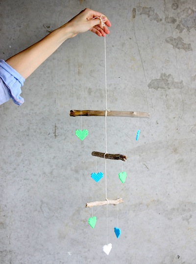 baby mobile made with melty bead hearts hanging from a branch